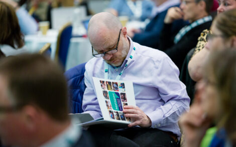 a man consults a natspec conference folder