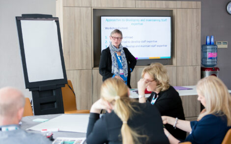 a woman presents with a flip chart to a group of delegates