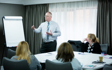 A man leads a workshop session with a flowchart