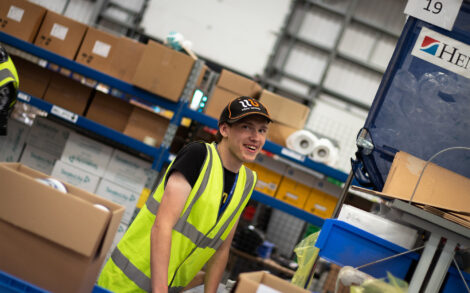 a learner in a hi-vis vest working on organising boxes