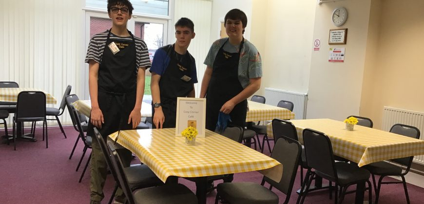Three students at Wargrave house standing smiling in neat aprons in a clean cafe environment with yellow check tablecloths