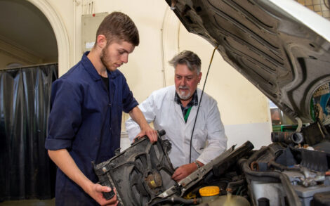 a student works fitting car parts whilst being overseen by a tutor