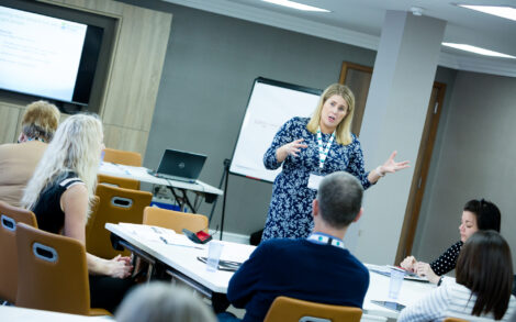 a woman presents a training session to a room
