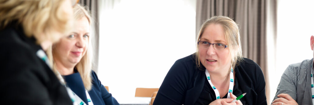 a woman engages in a conversation with colleagues around a round table