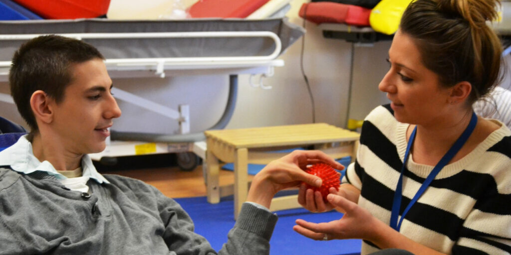 A learner engaging in a therapy session, handling a spiked plastic ball with his therapist