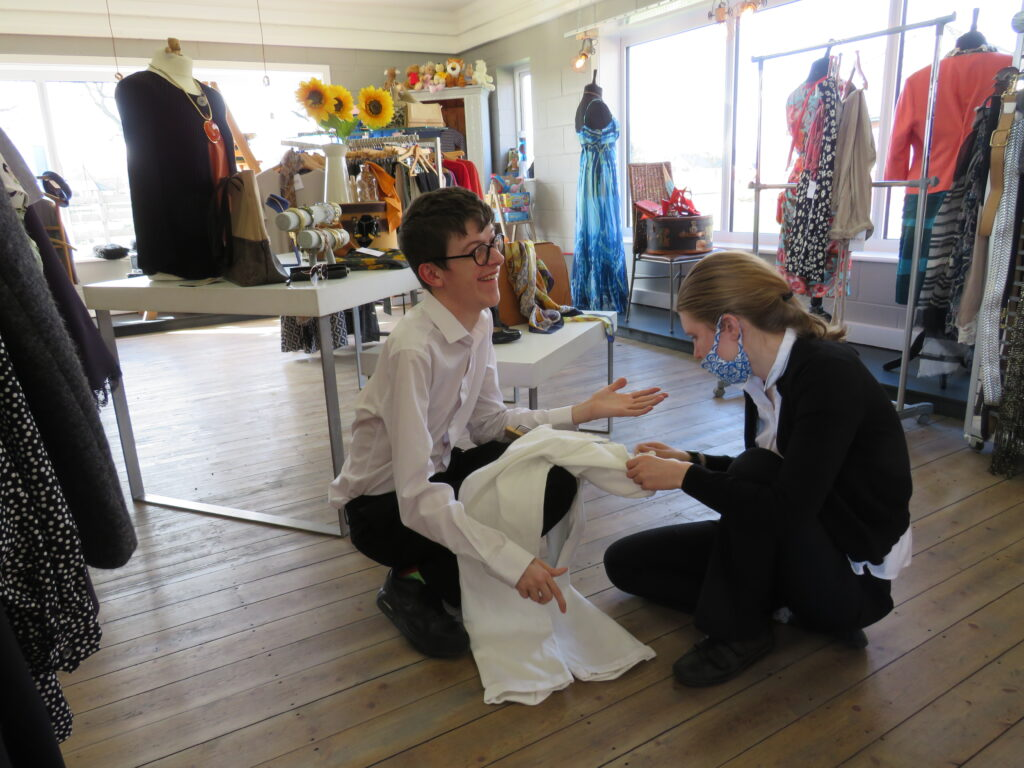 two students preparing some white trousers to go on display in Derwen's charity shop