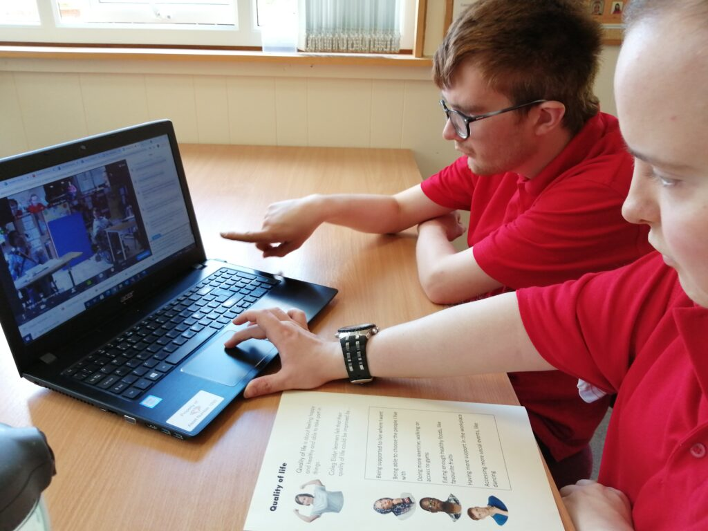 two students from Coleg Elidyr attend the student parliament meeting virtually. They have notes on the table of what they want to talk about