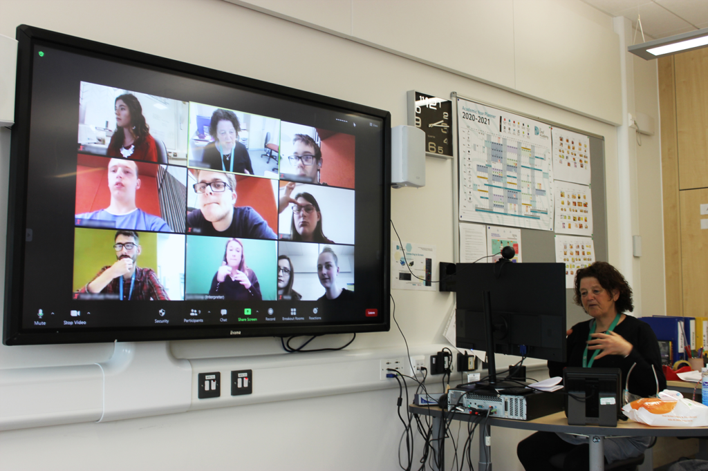 a teacher hosts a class on zoom. the screen is filled with many different pictures of students