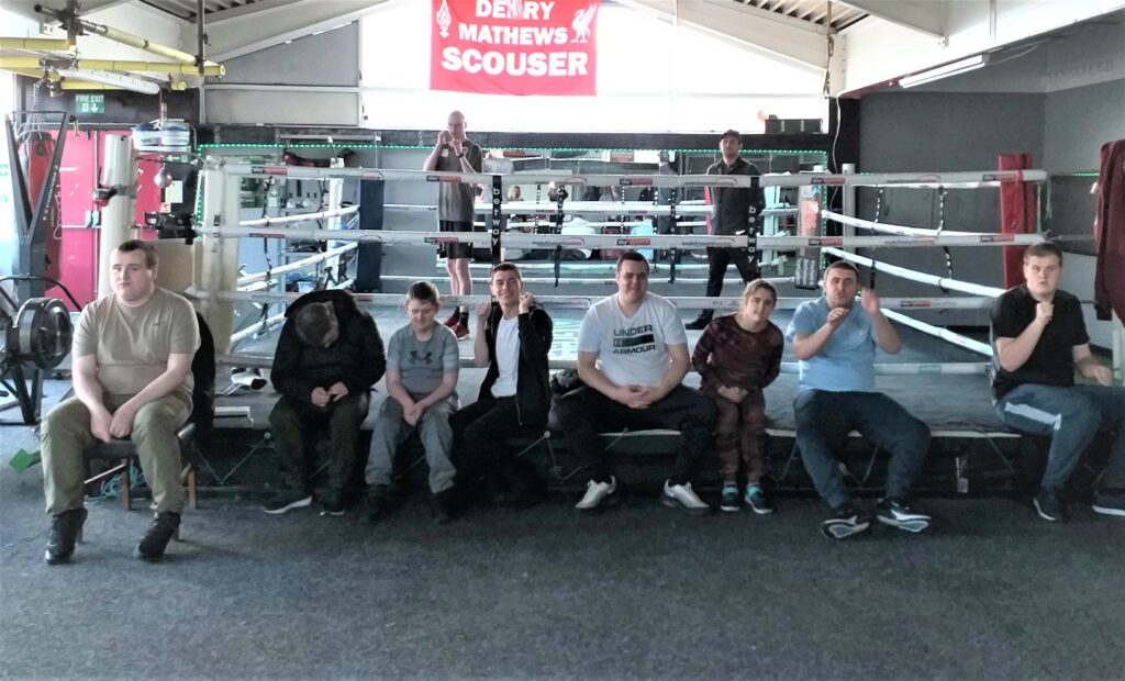 a group of students sitting on the edge of a boxing ring, looking happy and excited