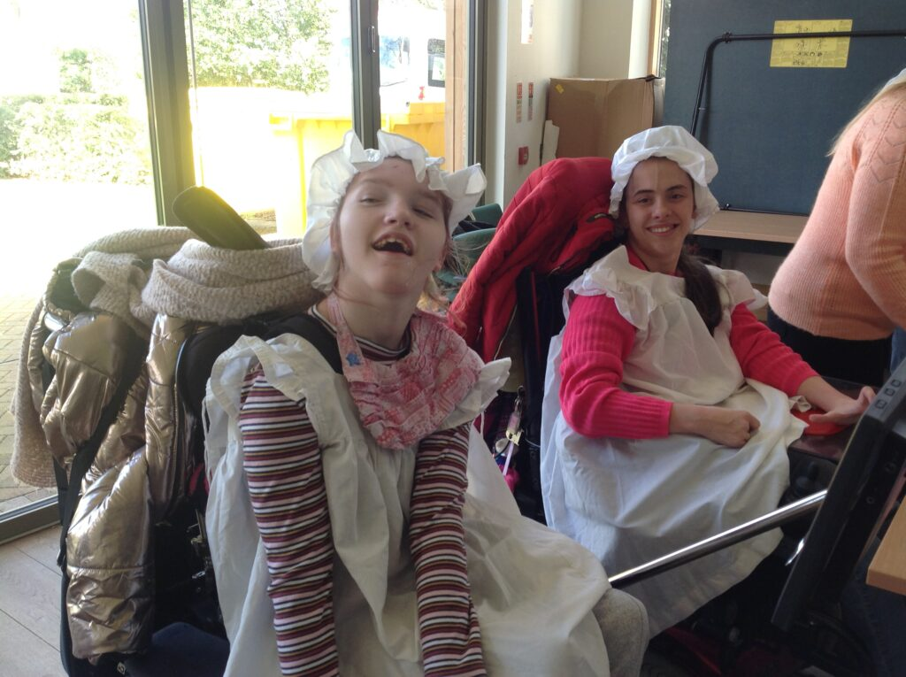 two students in wheelchairs enjoying trying on victorian costumes with white aprons and hats