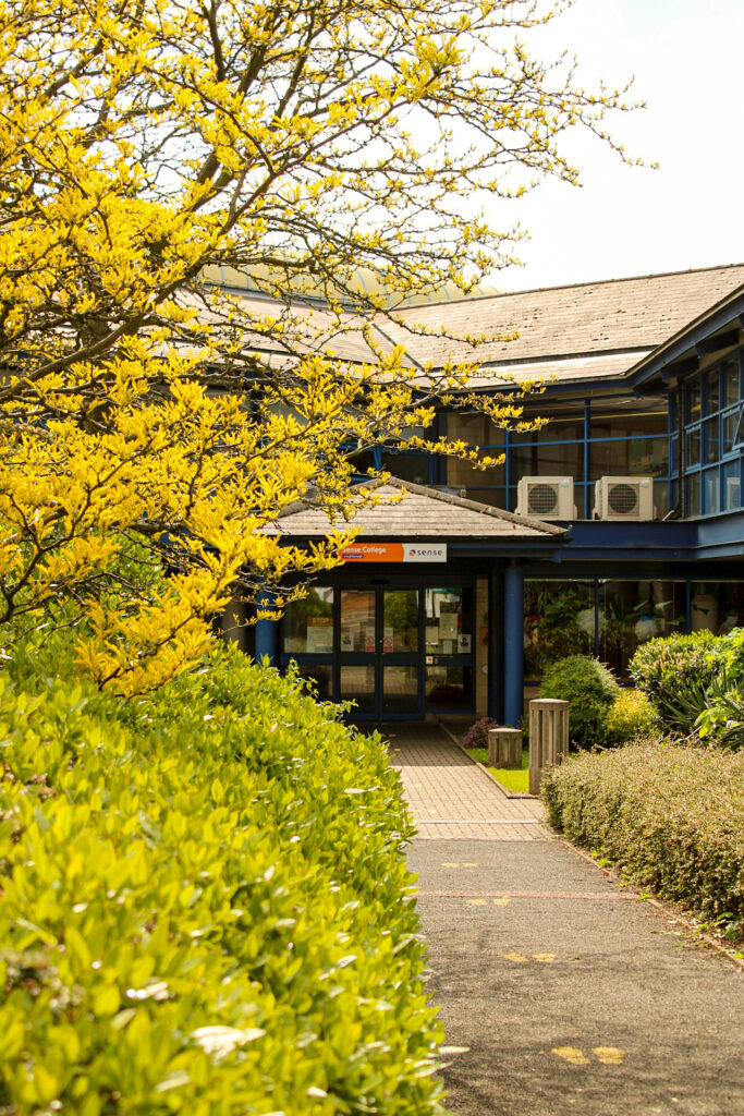 The outside of Sense College Loughborough, a brick building with lots of greenery outside.