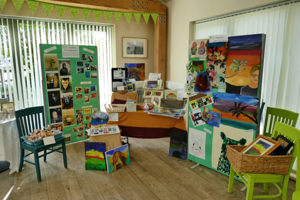 Fairfield Farm College's stall on the art trail, including two big boards or student art and photography, as well as baskets of greeting cards and pictures in frames.