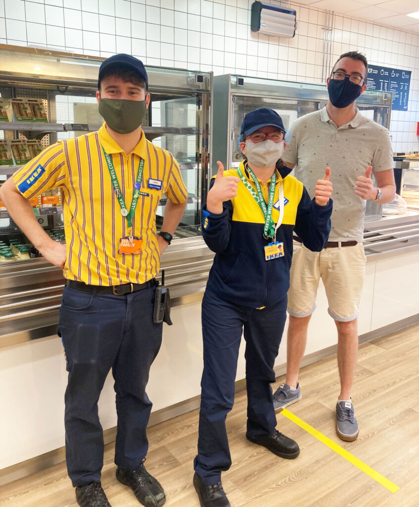 Nina, in her ikea uniform, standing with other members of staff. Nina is giving a thumbs up for the camera.