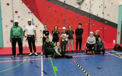 a group of QAC students in front of the gym climbing wall. they all look happy with their completed challeng