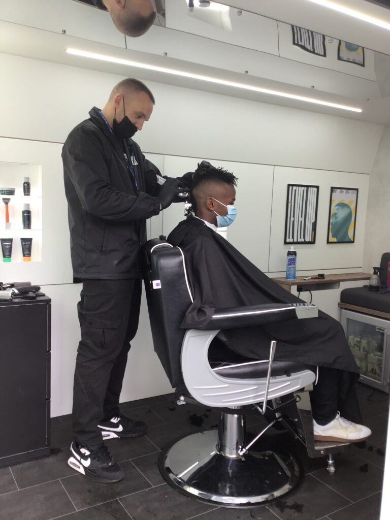 Barber Andy Nash cuts the hair of a student using a pair of clippers as the student sits in the barber's chair.
