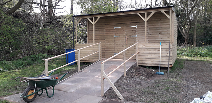 A large, wooden, outdoor shed, with a ramp leading up to it