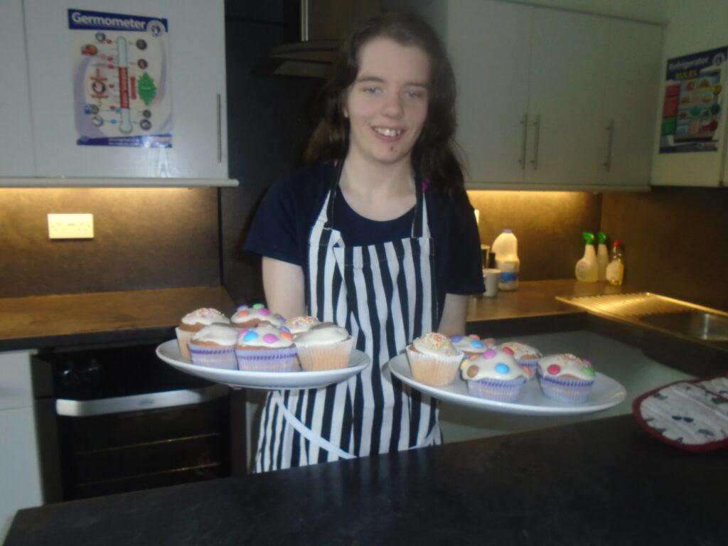 An ESPA student holding up two plates of iced cupcakes