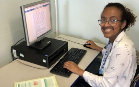 Sudio, smiling, working at a computer