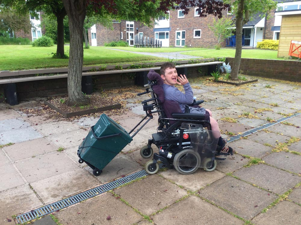 Liam rolls across a courtyard in his motorised wheelchair, tugging a recycling caddy that is attached to his wheelchair behind him. He is smiling in delight.