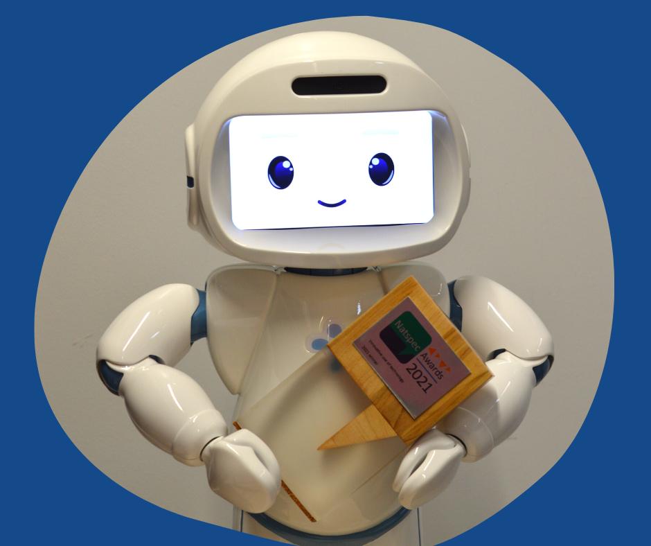 Bridge College's smiling QT robot holding a Natspec Awards trophy