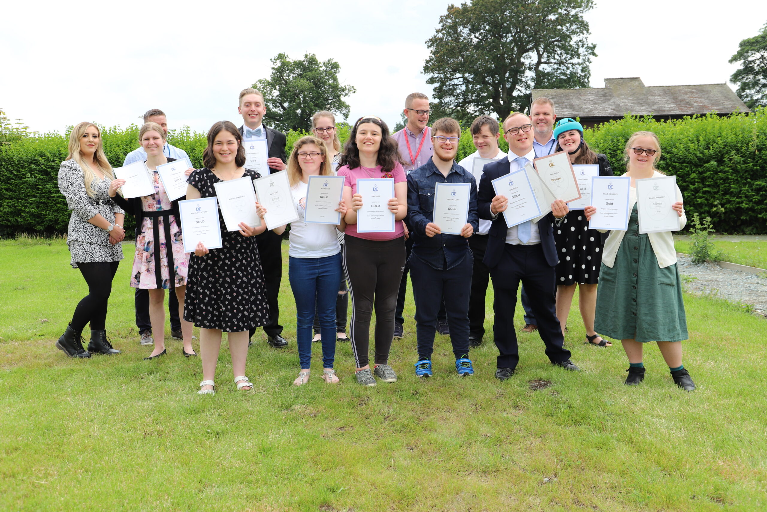students from Derwen College standing well dressed on the college lawn with the DofE gold certificates