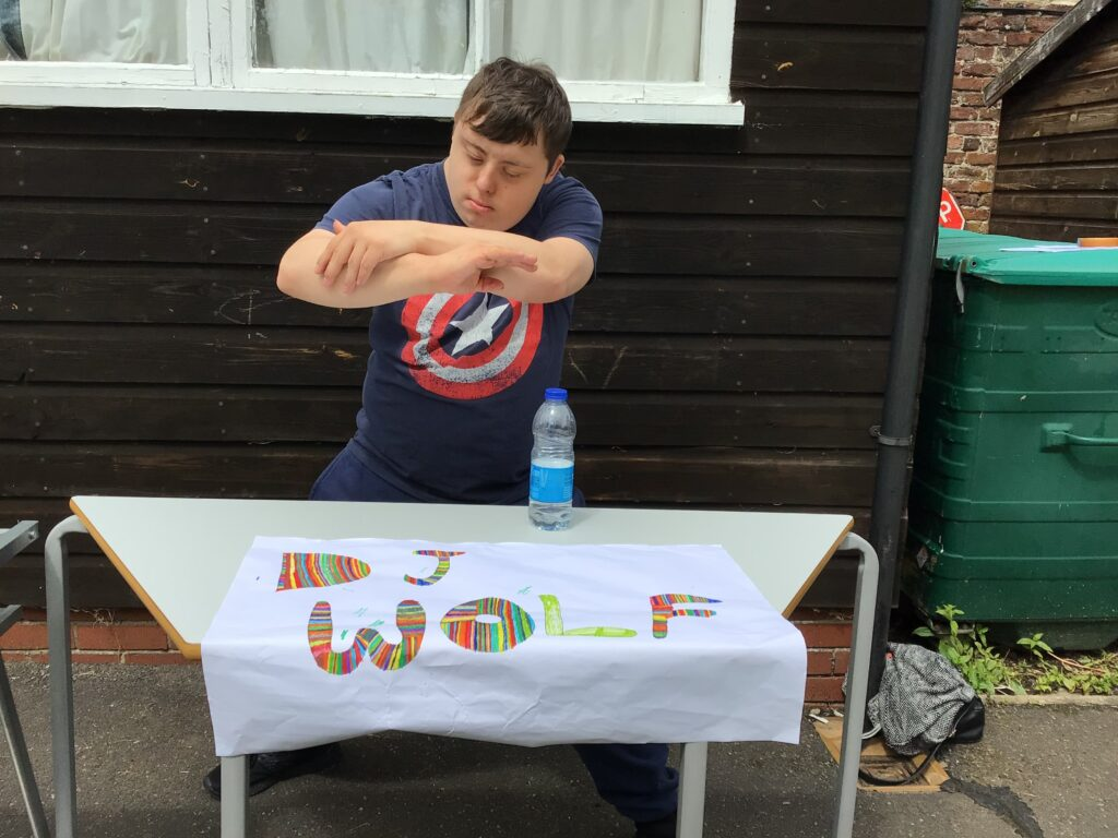 DJ Wolf, in a captain america t-shirt and with his sign, getting ready to accompany the sports day