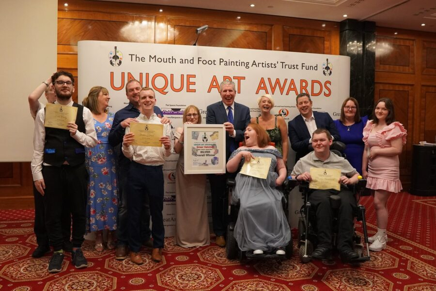 a large group of students, staff and families pose with their winners certificates at a fancy hotel