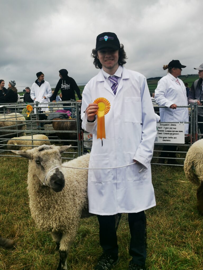 a student posing with a rosette and one of the award winning rams