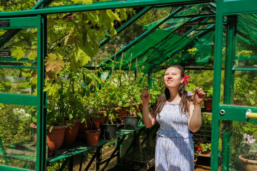 a smiling student looks up at the sun inside a greenhouse with lots of plants growing