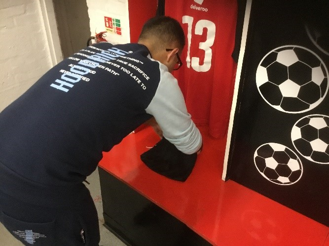 a student works folding clothes at redditch football club